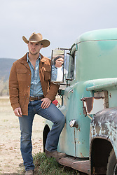 hot cowboy by an old truck with a reflection of a girl in the rear view mirror