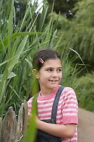 Girl (5-6) standing beside reeds
