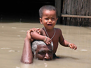 sebat ali mondal village man carries with her cousin under water in front of house at Kalair char village, about 305 kilometers southwest of Gauhati, capital of northeastern Indian state of Assam, thursday, July 10, 2003. Floods and mudslides in the northeastern states of Assam has killed at least 28 people over the past week and uprooted more than 500,000 from their homes, while 25 lakhs render homeless. (AP Photo/Shib Shankar Chatterjee)