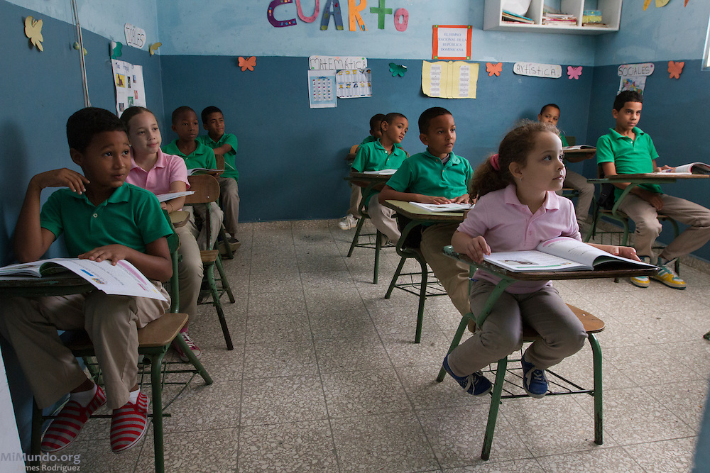 "Elementary school children attend a class at the Colegio Color de Vida, a school in Esperanza, Valverde, that has received Fairtrade premium funds via La Santa Cruz in order to pay for an after school homework program as well as school supplies for its 85 students. Antonia Mendoza, the school's founder and director, declares: ""Unfortunately the government does not cover all the educational needs in our municipalities. Without the money [from Fairtrade via La Santa Cruz] we would not be able to operate. They are our greatest support."" La Santa Cruz is an association of small producers in northern Dominican Republic that exports organic bananas certified by the Fairtrade Labelling Organization (FLO). As of December 2014, La Santa Cruz exports 100% of its total production via FLO to England, Germany, France and the Netherlands. Once La Santa Cruz finishes processing its organic certification, it hopes to export 100% of its production as organic bananas via FLO. Esperanza, Valverde, Dominican Republic. December 9, 2014."