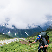 Todd hiking above the clouds on a knoll in the Boston Basin of the North Cascades