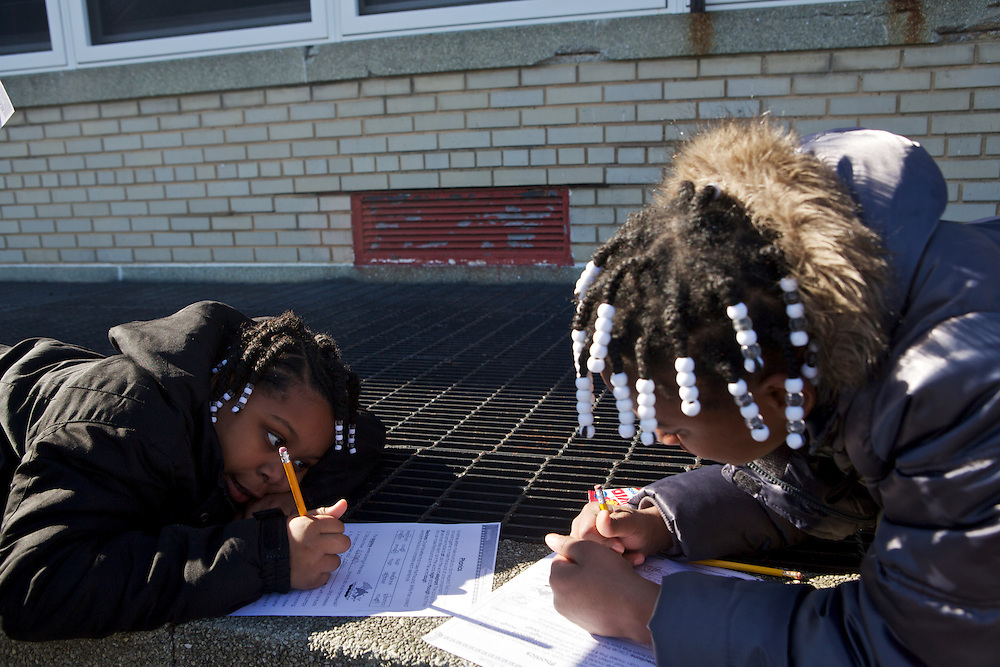 Taniya Hall, 10, left, and Faith Hamilton, 11, with their class work before they can participate in recess at Adelaide Davis Elementary School on Nov. 26, 2012 in Washington, D.C. Last week DCPS Chancellor Kaya Henderson proposed closing 20 under-enrolled schools in the District. Davis Elementary is one of 20 schools in the DCPS system included in the school closure proposal. ..CREDIT: Lexey Swall for The Wall Street Journal.DCSCHOOLS