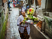 "02 AUGUST 2017 - UBUD, BALI, INDONESIA: A woman in Ubud walks to the ""Merchants' Day"" ceremony at the Pura (Temple) Melanting Pasar Ubud, the small Hindu temple in the Ubud market. It's a day that merchants throughout Ubud come to the temple to make offerings and pray for prosperity.    PHOTO BY JACK KURTZ"