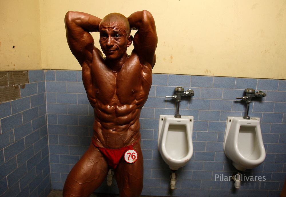 A competitor flexes his muscles inside a bathroom before a bodybuilding competition in Lima January 30, 2010.  REUTERS/Pilar Olivares (PERU - Tags: SOCIETY SPORT IMAGES OF THE DAY)