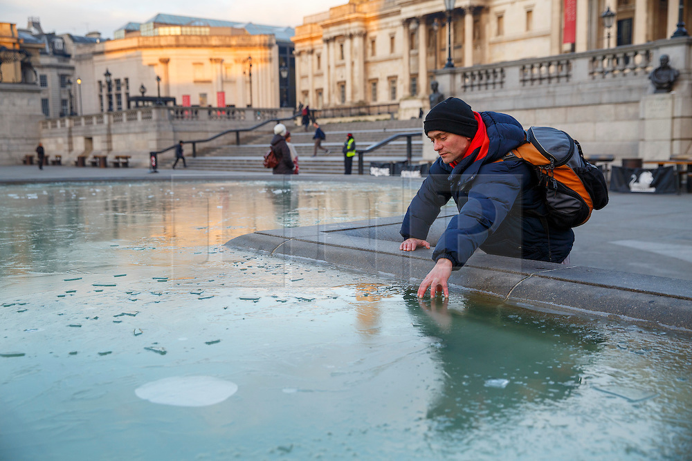 © Licensed to London News Pictures. 20/01/2016. London, UK. Commuters looking at the fountains in Trafalgar Square which covered in a layer of ice after temperatures in the capital dropped as low as -3C on Wednesday, 20 January 2016. Photo credit: Tolga Akmen/LNP