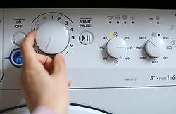 A person sets up a washing machine in a London home. Picture date: Wednesday April 1, 2020.