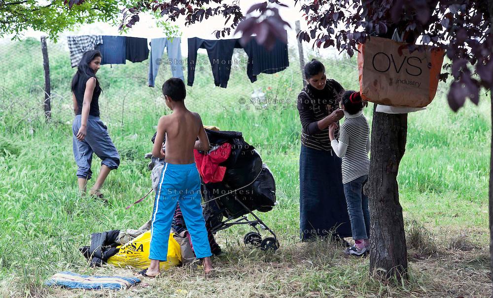Roma 29 Aprile 2011.Rom  romeni sgomberati dal campo  di via Severini in zona Tor Sapienza  il 18 Aprile dalle Forze dell'Ordine, vivono in 20 nuclei familiari  nel parco  di  via De Chirico dei 14 bambini che andavano a scuola solo una bambina  continua la frequenza. Mamma  veste i figli.