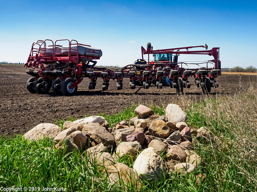 24 APRIL 2019 - PANORA, IOWA: A farmer drives his tractor past a pile of rocks on the edge of his field east of Panora, in central Iowa. With winter over, Iowa farmers are working their fields. Ninety percent of the land in Iowa is used for agricultural purposes. According to the USDA, there are more than 30 million acres of land in Iowa dedicated to farm use. More than 13 million acres used for corn production and about 10 million acres for soybeans. Iowa is one of the leading states in the US for production of corn, soybeans, and pork.        PHOTO BY JACK KURTZ