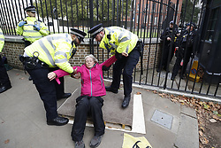 © Licensed to London News Pictures. 09/10/2019. London, UK. Armed police (R) look on as Extinction Rebellion activists are removed by police from their blockade near the back entrance to Downing Street during a third day of protests in central London. The climate change group intend to blockade the Westminster area for two weeks to demand that the government takes immediate and decisive action on climate change. Photo credit: Peter Macdiarmid/LNP