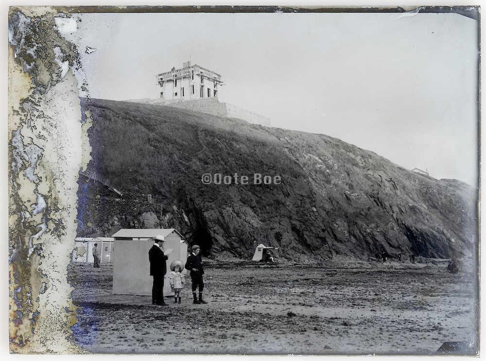 eroding glass plate early 1900s with family on beach near hotel