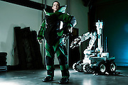 A U.S. Air Force explosive ordinance disposal team member dressed in his full bomb suite stands near his robot...The Airman uses the robot to disarm bombs remotely. Some bombs must be disarmed by a technician, so they wear bomb resistant suits.