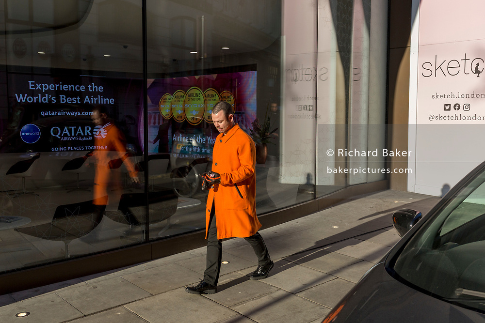 A man wearing an organge coat walks past the window of the Qatar Airlines office on Conduit Street in Mayfair, on 20th January 2020, in London, England.