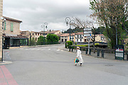 elderly woman with mask walking in empty street during Covid 19 crisis France Limoux April 2020