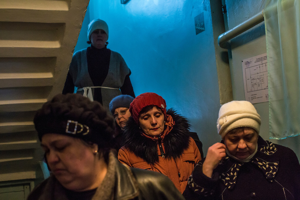 DONETSK, UKRAINE - JANUARY 23, 2015: Administrators and parents from School 337, which was struck and damaged two days earlier by a rocket attack, gather at the school to prepare the building for indefinite closure in Donetsk, Ukraine. Schools in Donetsk have been closed this week due to increased fighting, and will remain closed for the foreseeable future. After the rebels finally took control of the heavily contested airport in Donetsk from the Ukrainian Army, they have promised an offensive to extend their territory further. CREDIT: Brendan Hoffman for The New York Times