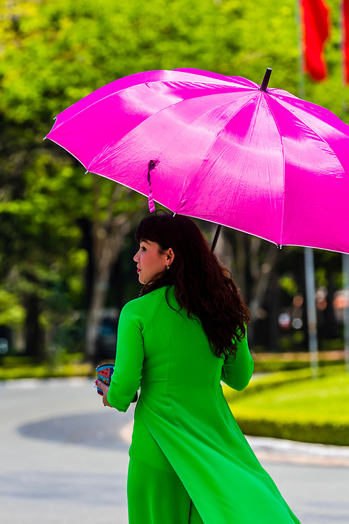 An elegant Vietnamese woman walks underneath her umbrella, Reunification Palace (formerly the Presidential Palace), Ho Chi Minh City (Saigon), Vietnam.