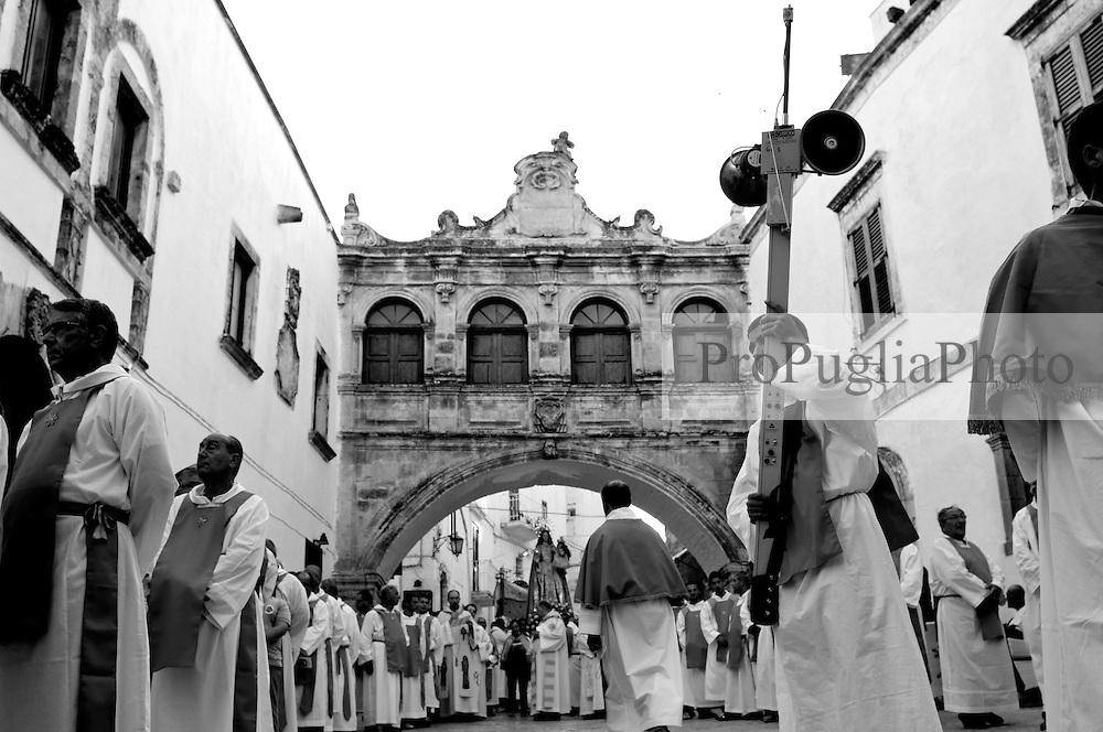 La processione della Madonna della Stella in Ostuni, ferma davanti alla Cattedrale, lascia il tempo di proclamare alcune preghiere ed intonare alcuni canti, prima di ricominciare a sfilare. I fedeli fanno quadrato sotto l'arco della curia vescovile