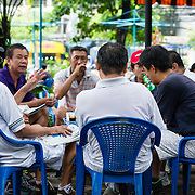 Vietnamese men gather at an outdoor cafe