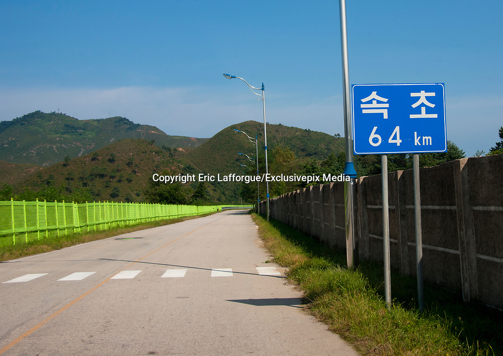 KUMGANG<br /> THE NORTH KOREAN GHOST TOWN<br /> <br /> The first town USA will find on his way to invade NK will be this ghost town where HUnday lost 1 billion USD..<br /> <br /> The Mount Kumgang tourist complex in North Korea, near the DMZ, was built in 1998 by the South Korean giant company Hyundai. The chaebol paid a fee of $1 billion to the North Korean government for 50 years of exclusivity. The cost of the 500-square kilometer complex was $400 million, including hotels, a spa, a fire station, a tourism office, a golf course, a supermarket, a clinic, tours in the mountain... Kumgang resort attracted nearly 2 millions south korean tourists from1998 to 2008.<br /> In July 2008 a South Korean tourist, Miss Park Wang-ja, was shot dead there and South Korea decided to stop all the tours in North Korea. The North Korean government said the tourist entered the military zone, and ignored the warnings from the north korean soldiers.<br /> So in retaliation, North Korea decided to seize the whole tourist complex. This decision was a real drama. Not for the touristic industry only, but for the separated families from the south and the north: Kumgang was also the place where hundreds of North and South Korean relatives were meeting each other for the first time in decades.<br /> For those reasons, since 2008, Mount Kumgang complex has became a ghost town. Only very few western tourists could visit the area.<br /> <br /> Photo shows:   The road leading to Kumgang was built for the tourists and is still sealed off all along by a high green wire fence, so the local people can not access the area and the tourist complex. A billboard just before arriving says that Seoul is only 64 km away.<br /> ©Eric Lafforgue/Exclusivepix Media