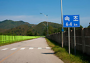 KUMGANG<br /> THE NORTH KOREAN GHOST TOWN<br /> <br /> The first town USA will find on his way to invade NK will be this ghost town where HUnday lost 1 billion USD..<br /> <br /> The Mount Kumgang tourist complex in North Korea, near the DMZ, was built in 1998 by the South Korean giant company Hyundai. The chaebol paid a fee of $1 billion to the North Korean government for 50 years of exclusivity. The cost of the 500-square kilometer complex was $400 million, including hotels, a spa, a fire station, a tourism office, a golf course, a supermarket, a clinic, tours in the mountain... Kumgang resort attracted nearly 2 millions south korean tourists from1998 to 2008.<br /> In July 2008 a South Korean tourist, Miss Park Wang-ja, was shot dead there and South Korea decided to stop all the tours in North Korea. The North Korean government said the tourist entered the military zone, and ignored the warnings from the north korean soldiers.<br /> So in retaliation, North Korea decided to seize the whole tourist complex. This decision was a real drama. Not for the touristic industry only, but for the separated families from the south and the north: Kumgang was also the place where hundreds of North and South Korean relatives were meeting each other for the first time in decades.<br /> For those reasons, since 2008, Mount Kumgang complex has became a ghost town. Only very few western tourists could visit the area.<br /> <br /> Photo shows:   The road leading to Kumgang was built for the tourists and is still sealed off all along by a high green wire fence, so the local people can not access the area and the tourist complex. A billboard just before arriving says that Seoul is only 64 km away.<br /> &copy;Eric Lafforgue/Exclusivepix Media