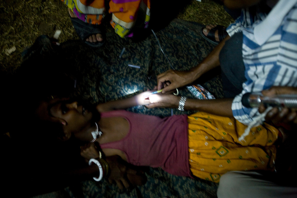 "A doctor administers an injection to a girl in torch light at a government refugee camp in Purnea, Bihar, India. The north Indian state of Bihar has a population density of 791 persons per sq Km, low literacy levels of 48% (2001 census) and a higly corrupt political system all of which has lead to a very poverty stricken state of affairs in the region. The ""Kosi"" river also called the ""Sorrow of Bihar"" flooded in end september 2008 due to mis-management by Governmnet authorities of a dam up north. The flooding displaced three districts and affected 30 million people. The people of Bihar were left stranded and helpless while the aid sent by the center and government was siphoned off by the corrupt system and litle trickled down to the common man. The flood victims were awaiting relief in refugee camps which did not even have proper living, lighting and sanitory conditions. The common man was left out in the darkness. ."