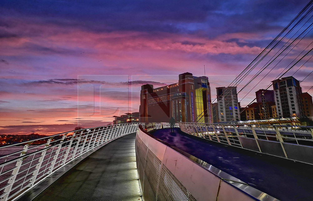 © Licensed to London News Pictures. 02/01/2020. Newcastle, UK. A bright sunrise on a winter morning over the River Tyne in Newcastle, north east England, with the Millennium Bridge (front) and Baltic Arts centre (rear) pictured. Photo credit: Colin Scarr/LNP