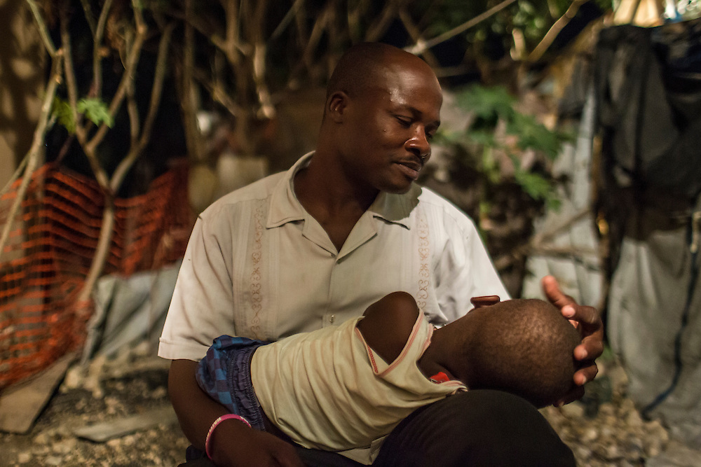 Louisno Clotaire holds his son Abinadab outside his house at the Corail-Cesselesse camp for people displaced by the 2010 earthquake on Saturday, December 20, 2014 in Port-au-Prince, Haiti. Clotaire is the camp's housing director, though he has not been paid his salary by the Croix-des-Bouquets mayor's office since he started the job a year ago. The camp is home to tens of thousands of people, for most of whom there is no work or easy access to the center of town, some 18 kilometers away.