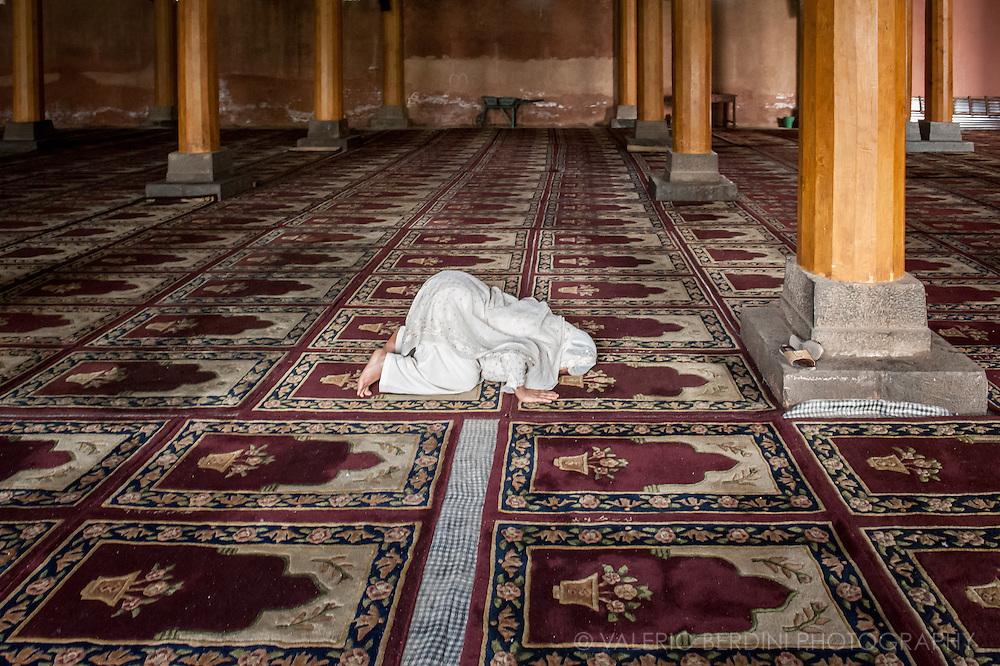 A solitary woman praying facing Mecca in the Jamia Masjid in Srinagar, Kashmir. India. 4 May 2010