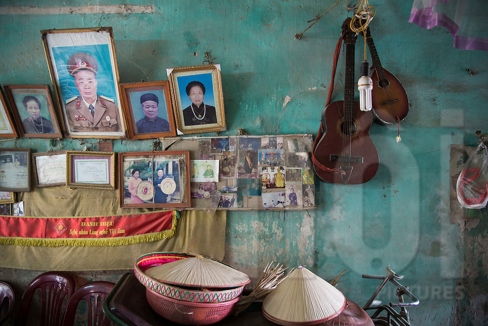 """A wall devoted to family photos and meaningful items in a home of Chuong Village, Ha Tay Province, Vietnam, Southeast Asia, 2013. This handicraft village specializes in the fabrication of the conical hat, known as """"non"""" in Vietnamese."""