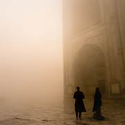 Figures in fog at Taj Mahal, India