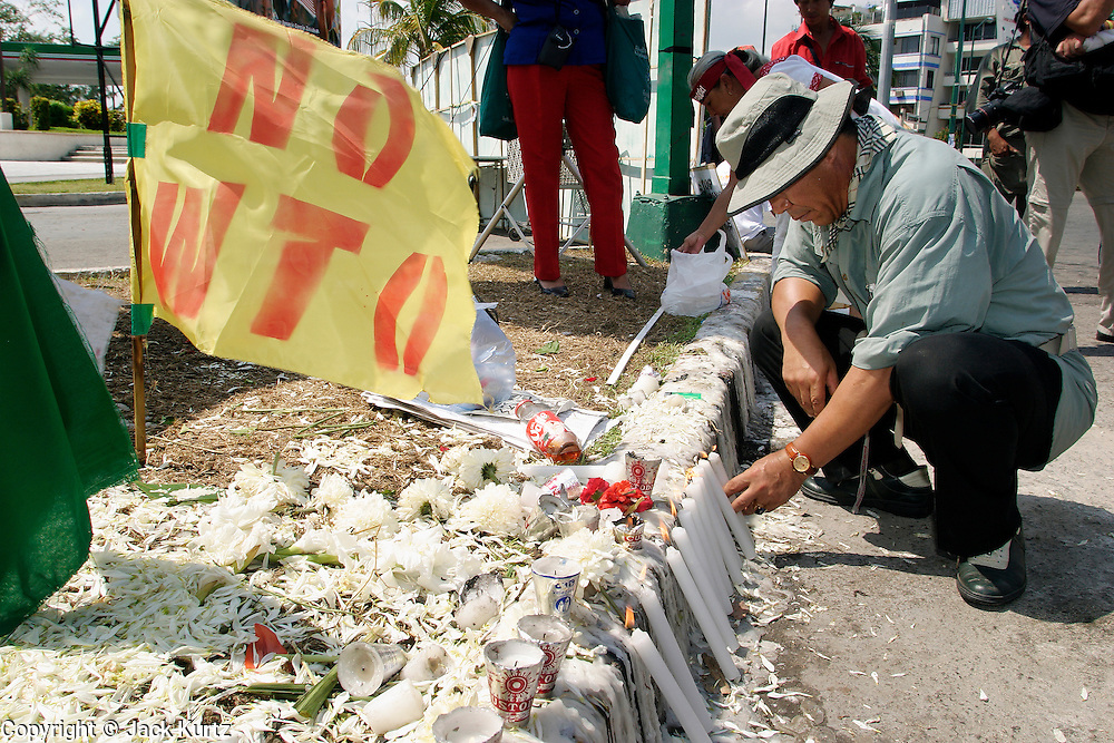 14 SEPTEMBER 2003 - CANCUN, QUINTANA ROO, MEXICO:  A Korean man lights candles Sunday at a shrine dedicated to Lee Kyung-hae, a Korean farm activists who publicly committed suicide Wednesday in Cancun to protest World Trade Organization agricultural policies, has been built where he died in a park in Cancun. Thousands of protestors opposed to the World Trade Organization and globalization have come to Cancun to protest the WTO meetings taking place in the hotel zone. Mexican police restricted most of the anti-globalization protestors to downtown Cancun, about five miles from the convention center.  PHOTO BY JACK KURTZ