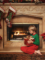 8 year old boy sitting beside the fireplace with a wrapped Christmas gift in his lap