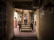 24 FEBRUARY 2015 - PHNOM PENH, CAMBODIA: People in a hallway in the White Building in Phnom Penh. The White Building, the first modern apartment building in Phnom Penh, originally had 468 apartments, and was opened the early 1960s. The project was overseen by Vann Molyvann, the first Cambodian architect educated in France. The building was abandoned during the Khmer Rouge occupation. After the Khmer Rouge were expelled from Phnom Penh in 1979, artists and dancers moved into the White Building. Now about 2,500 people, mostly urban and working poor, live in the building. Ownership of the building is in dispute. No single entity owns the building, some units are owned by their occupants, others units are owned by companies who lease out apartments. Many of the original apartments have been subdivided since the building opened and serve as homes to two or three families. The building has not been renovated since the early 1970s and is in disrepair. Phnom Penh officials have tried to evict the tenants and demolish the building but residents refuse to move out.   PHOTO BY JACK KURTZ