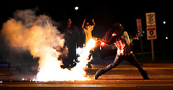 August 13, 2014 - Ferguson, Missouri, U.S. - A demonstrator, EDWARD CRAWFORD, returns a tear gas container shot by tactical police officers after they worked to break up a group of bystanders on Chambers Road near West Florissant. On this night protesters attempted to throw Molotov cocktails, rocks and bottles at police. This was the fourth straight night police used tear gas to disperse crowds protesting the fatal police shooting of unarmed teenager Michael Brown  on previous Saturday. (Credit Image: © Robert Cohen/St. Louis Post-Dispatch/zReportage.com via ZUMA Press)