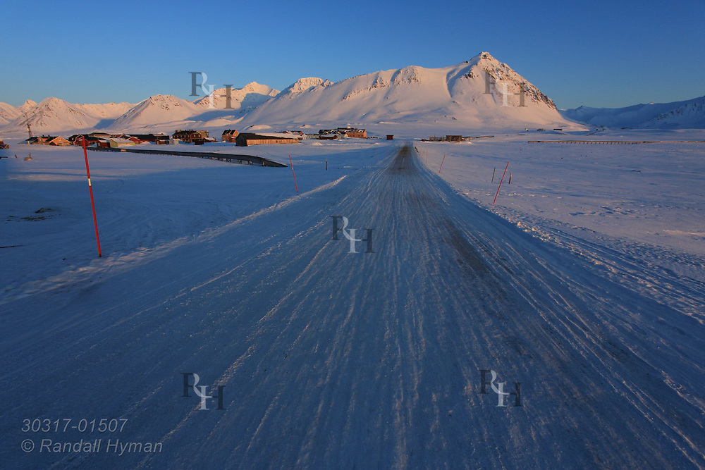 Icy road from airport leads to the international science village of Ny-Alesund on Spitsbergen island in April in Kongsfjorden; Svalbard, Norway.