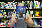 A man holds a copy of the children's book, The Gruffalo's Child in front his face. He is standing in front of a bookshelf full of books. HMP Kingston, Portsmouth, United Kingdom. As part of the Storybook Dads Program a prisoner reads a story for his 4-year-old son. HMP Kingston.