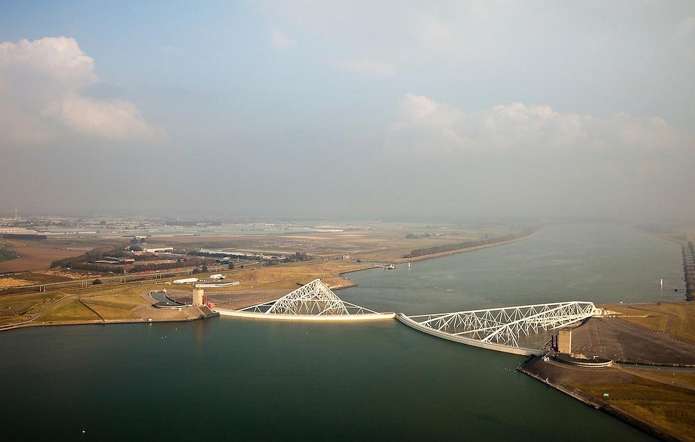 Nederland, Zuid-Holland, Nieuwe Waterweg, 19-09-2009; Functioneringssluiting Maeslantkering: de waterkering in de Nieuwe Waterweg wordt een maal per jaar, voordat het stormseizoen begint, getest. Tijdens  het sluiten van de kering ligt alle scheepvaartverkeer naar de Rotterdamse haven stil. Links van de Nieuwe Waterweg de kassen van het Westalnd en Maassluis. De Maeslantkering sluit normaal gesproken alleen bij dreigende stromvloed en bij een waterstand van 3 meter of meer boven NAP. De kering, onderdeel van de Deltawerken, vormt samen met de Hartelkering de Europoortkering en beschermt Rotterdam en achterland bij extreme waterstanden. .Netherlands, Hoek van Holland - Rotterdam harbour. Aerial view of the new storm surge barrier (Maeslantkering) in the Nieuwe waterweg during the so-called functioning closure, taking place one a year before the storm season begins. The waterway, leading to the Port of Rotterdam (at the horizon), is closed during the test..luchtfoto (toeslag), aerial photo (additional fee required).foto/photo Siebe Swart
