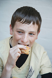 White youth eating a donut.