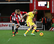 Milton Keynes Dons midfielder Carl Baker trying to keep the ball away from Brentford midfielder Konstantin Kerschbaumer during the Sky Bet Championship match between Brentford and Milton Keynes Dons at Griffin Park, London, England on 5 December 2015. Photo by Matthew Redman.