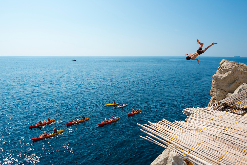 An Australian backpacker hurls his body off the rocky wall in the Old City of Dubrovnik, Croatia, soon to splash down beside a group on a kayak tour.