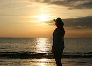 Woman in cowboy hat, silhouette,  gazing at beach sunrise, sunset at Jekyll Island, Georgia.