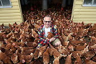 Robert Kramer, of Lake Meadow Naturals egg farm, kneels with his chickens in Ocoee, Fla., Tuesday, Feb. 9, 2016. (Photo by Phelan M. Ebenhack)