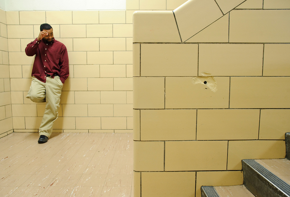 (photo by Matt Roth).Friday, May 14, 2010..Baltimore Freedom Academy Child Study Team member Travis Watkins stands in a stair well. In front of him is a hole where a rail used to be. The building housing the Baltimore Freedom Academy, a grade 6-12 Baltimore public charter school focusing in social justice, was built in 1960. Fifty years later, the school is in disrepair. Old pipes make water from the fountains undrinkable. Asbestos makes repairing/replacing the pipes a hazard. The school has no air conditioning which makes the year-round school unbearable in the summer. The most derelict area is the boys locker room, where students are not allowed.