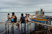 April 20, 2014 - Tacloban, Philippines. A group of young men relax on a wooden fishing pier over the easter weekend. Typhoon Haiyan struck the central Philippines on November 8, 2013, leaving more than 5000 dead and displacing nearly 2 million people homeless.