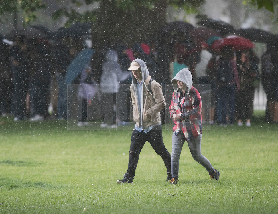 © Licensed to London News Pictures. 12/07/2016. London, UK. Two youths walk through St James' Park as a sudden rain storm hits central London as others shelter under a tree. Photo credit: Peter Macdiarmid/LNP