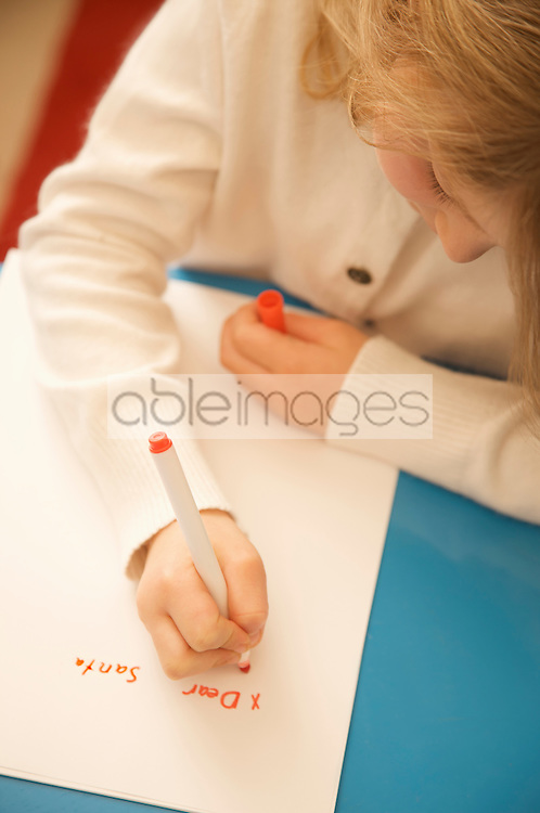 Close up of a girl writing a letter to Father Christmas