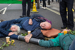London, UK. 7 October, 2019. Climate activists from Extinction Rebellion use an arm tube and superglue to block a road in Westminster on the first day of International Rebellion protests to demand a government declaration of a climate and ecological emergency, a commitment to halting biodiversity loss and net zero carbon emissions by 2025 and for the government to create and be led by the decisions of a Citizens' Assembly on climate and ecological justice.