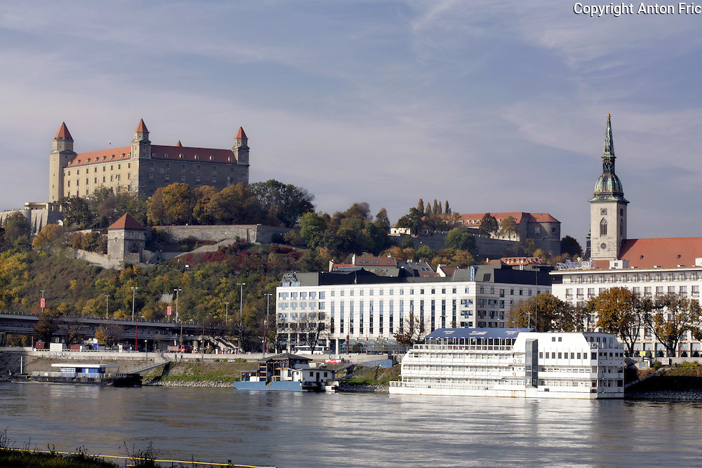 Bratislava castle in Bratislava - Capital city of Slovakia overlooking the river Danube. Picture taken from the right Danube river bank called Petrzalka. Hotel Dunaj (Danube) can be seen under the castle.