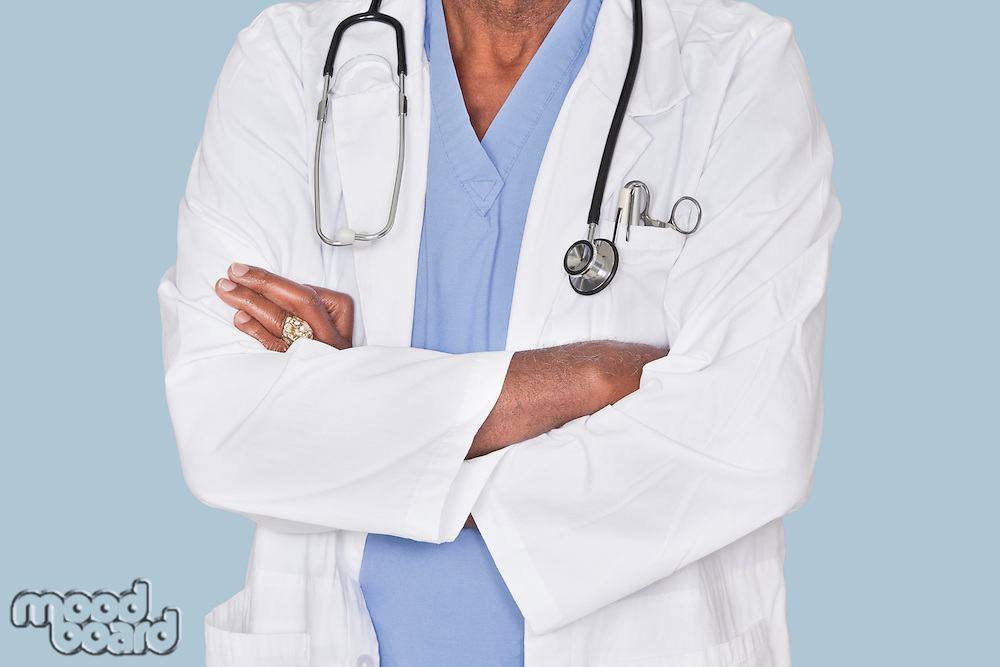 Midsection of a doctor with arms crossed over light blue background