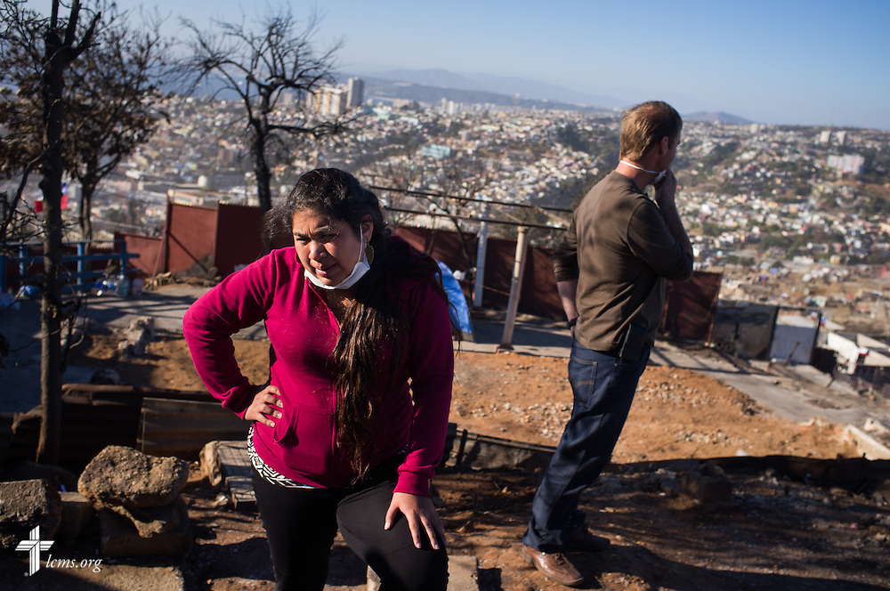 A woman stands on the plot of her destroyed home on Monday, April 21, 2014, on a hillside of homes affected by a devastating fire in Valparaíso, Chile. The catastrophic fire that tore through the hillsides above the historic port city fire killed 15 people, destroyed about 3000 homes, and left approximately 15,000 people homeless.  LCMS Communications/Erik M. Lunsford