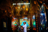 A man lights incense at Ong Pagoda in Can Tho, in the Mekong Delta in southern Vietnam.